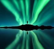 Borealis, άτομο και λίμνη αυγής με την αντανάκλαση ουρανού στο νερό στοκ εικόνες