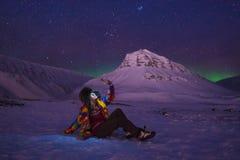 在挪威旅行博客作者女孩斯瓦尔巴特群岛的北极北极光极光borealis天空星在朗伊尔城市月亮山 免版税库存图片