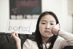 Bored. Little asian girl holding a sign that says bored Royalty Free Stock Image