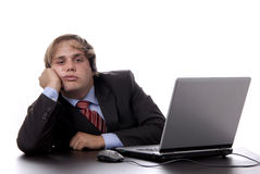Bored. Young bored business man working with is laptop Royalty Free Stock Photo