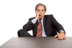 Bored. Mature business man on a desk, isolated on white Stock Images