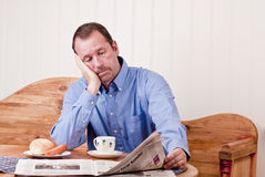 Bored adult man. At breakfast table dreaming Stock Photography