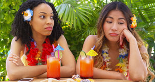 Bored African American and Asian women on vacation Royalty Free Stock Photo