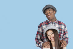 Bored African American man with smiling girlfriend over blue background Stock Photo