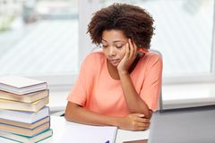Bored african american woman doing homework home Stock Photo