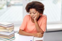 Bored african american woman doing homework home Stock Photo