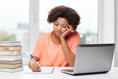 Bored african american woman doing homework home Stock Image