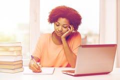 Bored african american woman doing homework home Stock Photos