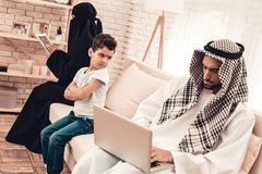 Bored Arabian Boy Sitting with Family on Sofa royalty free stock photos