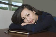 Bored Asian Businesswoman With Head On Desk Stock Image