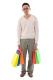 Bored Asian man holding shopping bags. Bored Asian man shopper holding shopping bags waiting for his girlfriend standing isolated over white background royalty free stock photo
