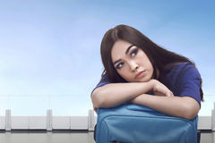 Bored asian tourist woman waiting with luggage Royalty Free Stock Photography