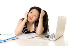 Bored asian woman student overworked on computer. Young pretty chinese asian student woman bored tired over worked on her laptop wearing a black shirt on a white Stock Image