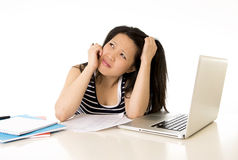 Bored asian woman student overworked on computer. Young pretty chinese asian student woman bored tired over worked on her laptop wearing a black shirt on a white Royalty Free Stock Images