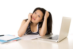 Bored asian woman student overworked on computer. Young pretty chinese asian student woman bored tired over worked on her laptop wearing a black shirt on a white Stock Images