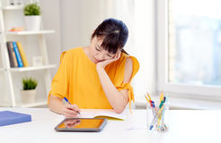Bored asian woman student with tablet pc at home Stock Photo