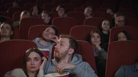 Bored audience leaving cinema while session in slow motion. Uninteresting film