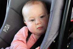 Bored baby in a car seat royalty free stock images