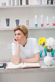 Bored beautician waiting at reception Stock Photography