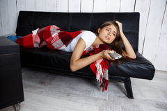 Bored beautiful girl watching tv, lying on sofa at home. Royalty Free Stock Photos