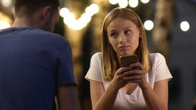 Bored beautiful young woman on bad date using her phone. stock video footage