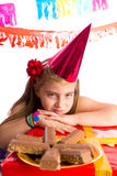 Bored blond kid girl in party with chocolates. Bored gesture blond kid girl in party with chocolates and birthday hat Stock Photography