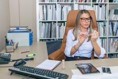 Bored blonde secretary polishing nails in the office Stock Photos