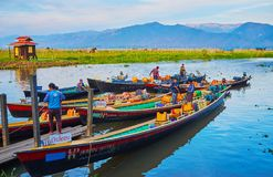 The bored boaters, Inle Lake, Myanmar. YWAMA, MYANMAR - FEBRUARY 18, 2018: The bored boaters wait the tourists at the Nga Phe Chaung Monastery of jumping cats Royalty Free Stock Photos