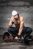 Bored bodybuilder talking on the phone Royalty Free Stock Image