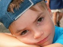 Bored boy. A young boy rests his face on his arms, looking bored Royalty Free Stock Photography