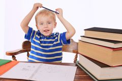Bored boy at a desk Royalty Free Stock Image
