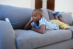 Bored boy looking at mobile phone while lying on gray sofa Royalty Free Stock Image