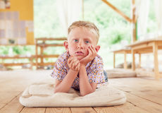 Bored boy lying on the wooden terrace on summer day Royalty Free Stock Image