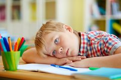 Bored boy. Bored or pensive schoolboy lying on desk Royalty Free Stock Photography