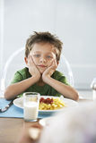 Bored Boy Sitting At Breakfast Table Stock Photos