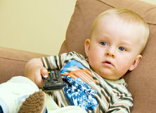 Bored boy watching TV. Bored baby boy watching TV with black remote control. Boy is sitting on brown sofa Royalty Free Stock Photos