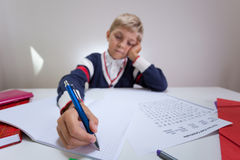 Bored boy writing in notebook Royalty Free Stock Images