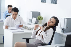 Bored business lady. Bored Vietnamese business lady dreaming at her workplace Royalty Free Stock Photo