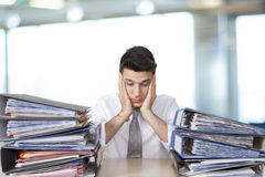 Bored businessman in office with files Stock Images