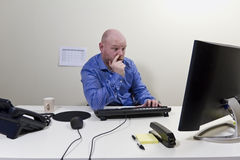 Bored Businessman picking Nose. Bored businessman / office worker in his office royalty free stock photo