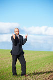 Bored businessman pointing upwards to copyspace Stock Image