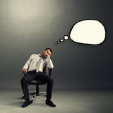 Bored businessman with speech bubble. Bored businessman sitting on the chair with empty speech bubble over grey background Stock Images