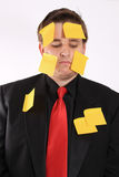 Bored businessman with sticky note paper Royalty Free Stock Images