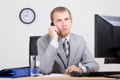 Bored businessman talking on phone in office Stock Image