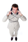 Bored businessman tangle up in phone wires. Isolated on a white background Royalty Free Stock Photography
