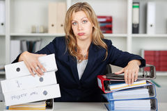 Bored Businesswoman Behind Stacked Binders At Desk Stock Photography