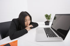 Bored businesswoman looking at laptop in office Royalty Free Stock Images