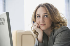 Bored Businesswoman Working in Office. A young businesswoman slouches at her desk with a bored expression on her face.  Horizontal shot Stock Photos