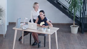 Bored businesswomen looking away while sitting on chair stock footage