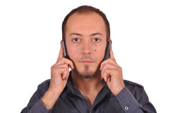 Bored busy guy with two cellphones Royalty Free Stock Photography